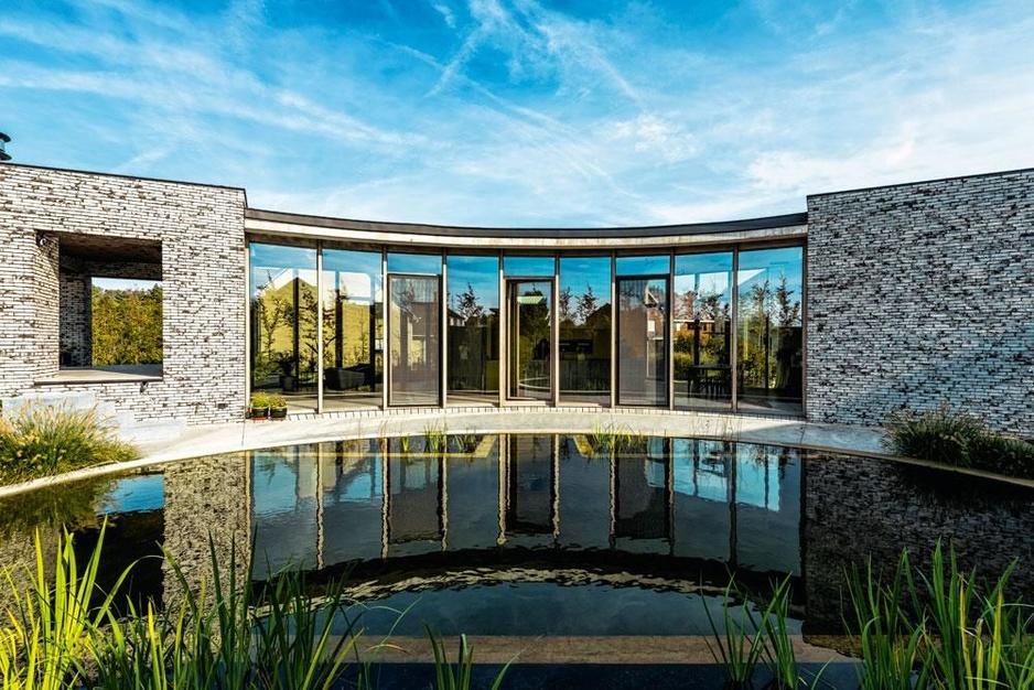 Veel glas en hout, geen rechte lijnen: dit huis in Muizen verrast en ademt vakantie