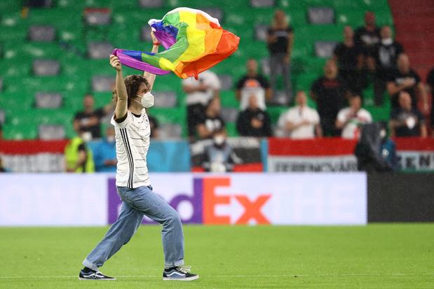 Activist met regenboogvlag op veld tijdens Hongaars volkslied
