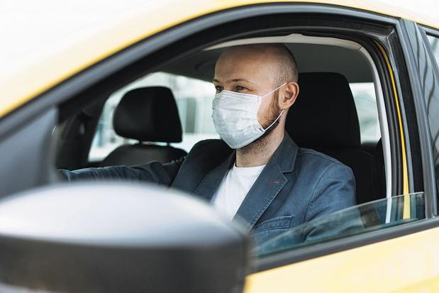 Met een mondmasker achter het stuur