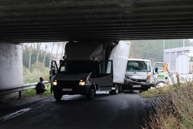 Lichte vrachtwagen klem onder brug langs Lovaart