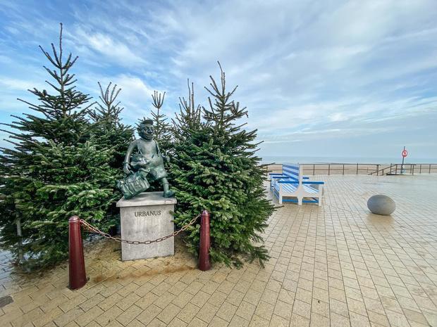 Stripheld Urbanus op de Zeedijk omringd door vroege kerstbomen