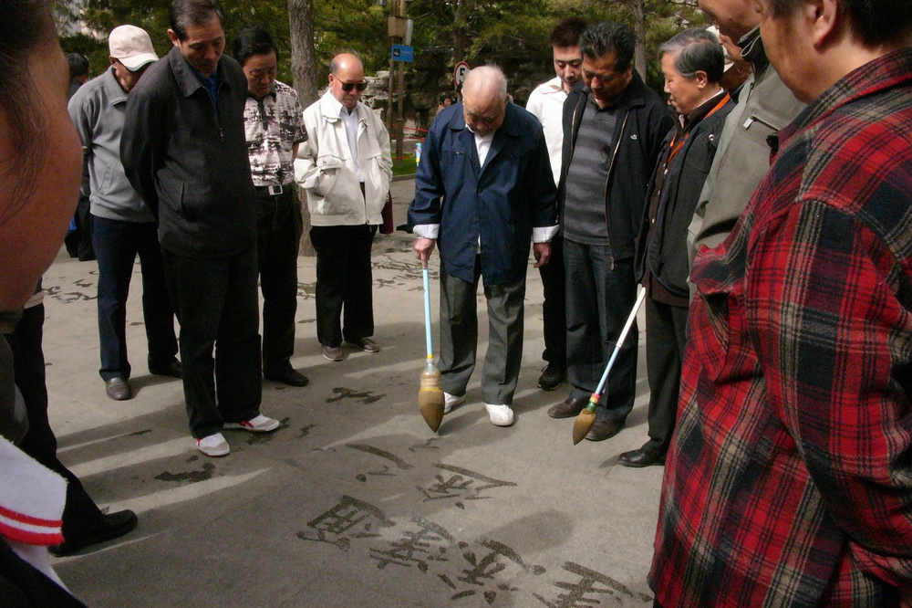 Peking, Chaoyang park: een oude man tekent oude Chinese karakter met water op de grond. Toeloop van jongeren die die karakter vergaten. Onbewust passief verzet tegen het nieuwe China dat hen opgedrongen wordt?, Maria Fialho