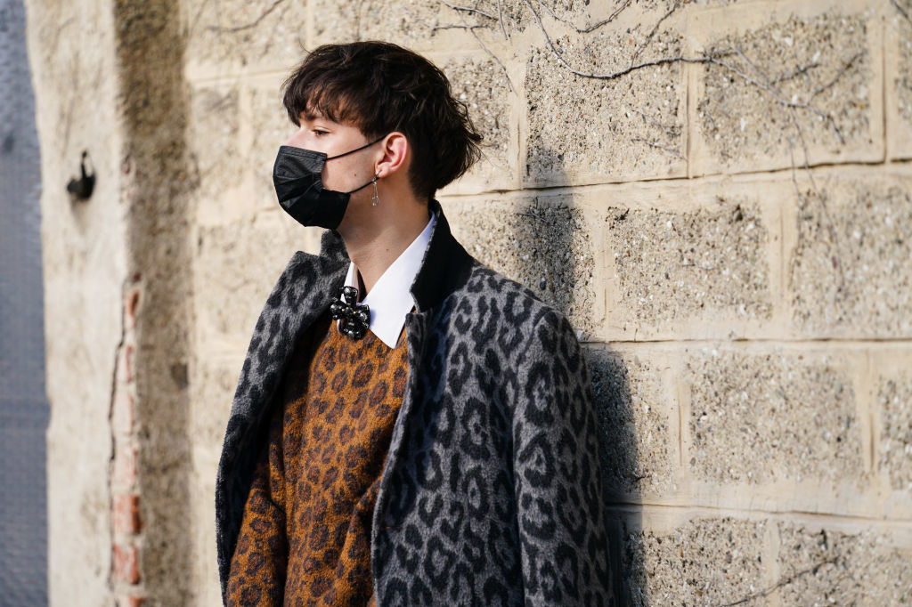 Un invité porte un masque noir, un manteau gris imprimé léopard, un pull brun en laine imprimé léopard, une chemise blanche, à l'extérieur de BOSS, pendant la Fashion Week de Milan automne/hiver 2020-2021, Getty Images