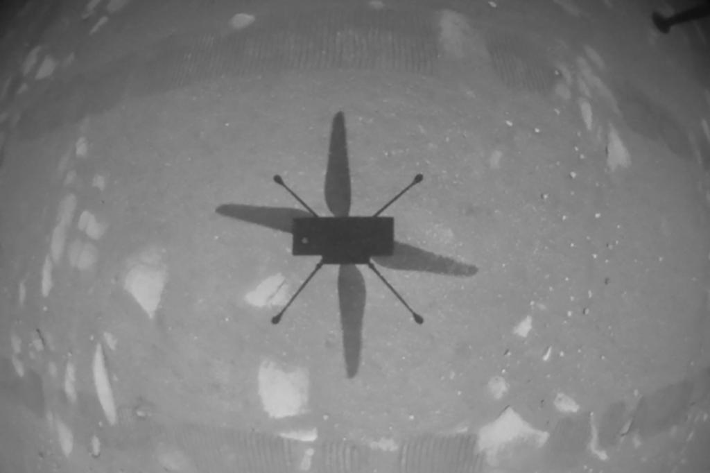 Ingenuity stuurde een zwart-witfoto door waarop de schaduw van het toestel te zien is op het Marsoppervlak., Nasa
