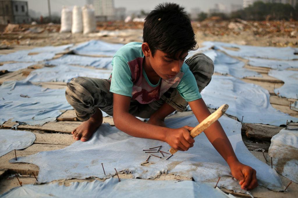 Angur (11) werkt als leerlooier voor een dollar per dag in Keraniganj, Dhaka, Bangladesh, Getty
