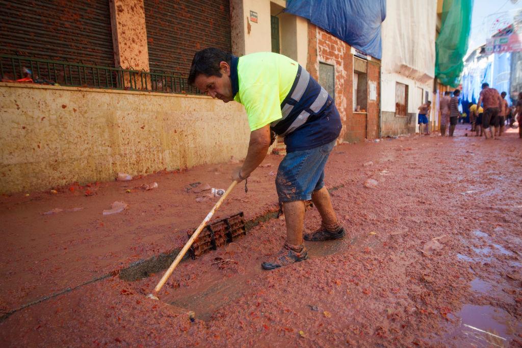 Een schoonmaker aan het werk na La Tomatina 2019., Getty