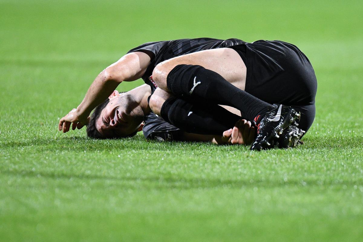 Een beeld dat we wel vaker zien: een voetballer die het uitkermt van de pijn., BELGAIMAGE