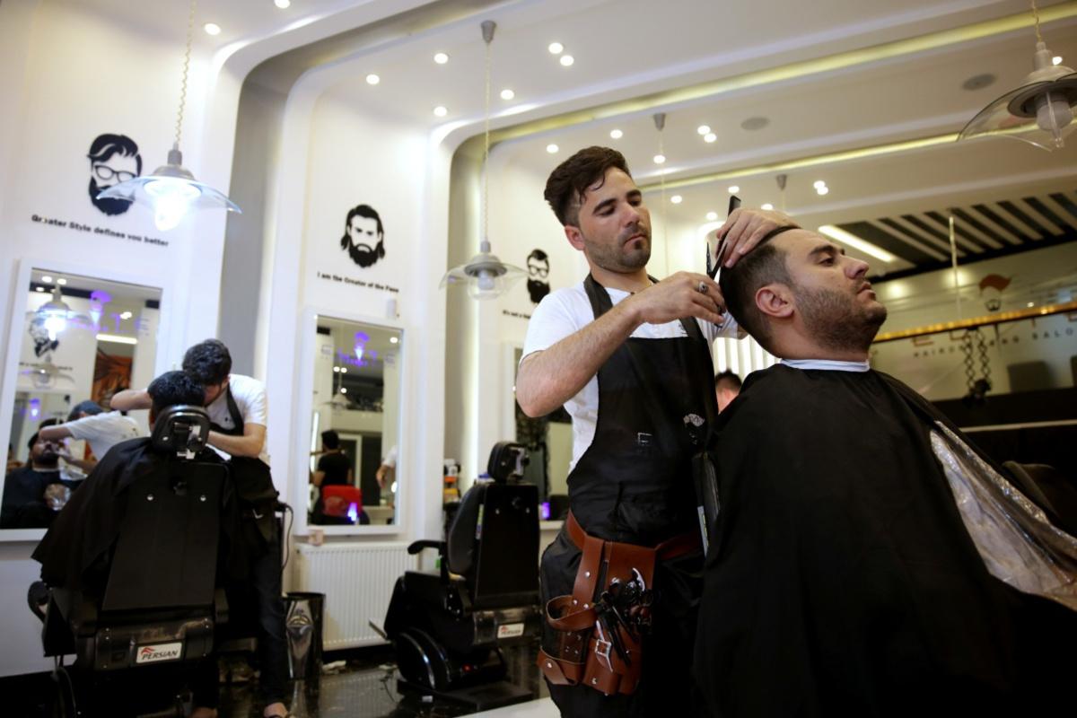 Kapper in Kaboel. Duizenden Afghanen die voor in het land verblijvende buitenlanders werkten zijn plotseling hun werk kwijt. , Reuters