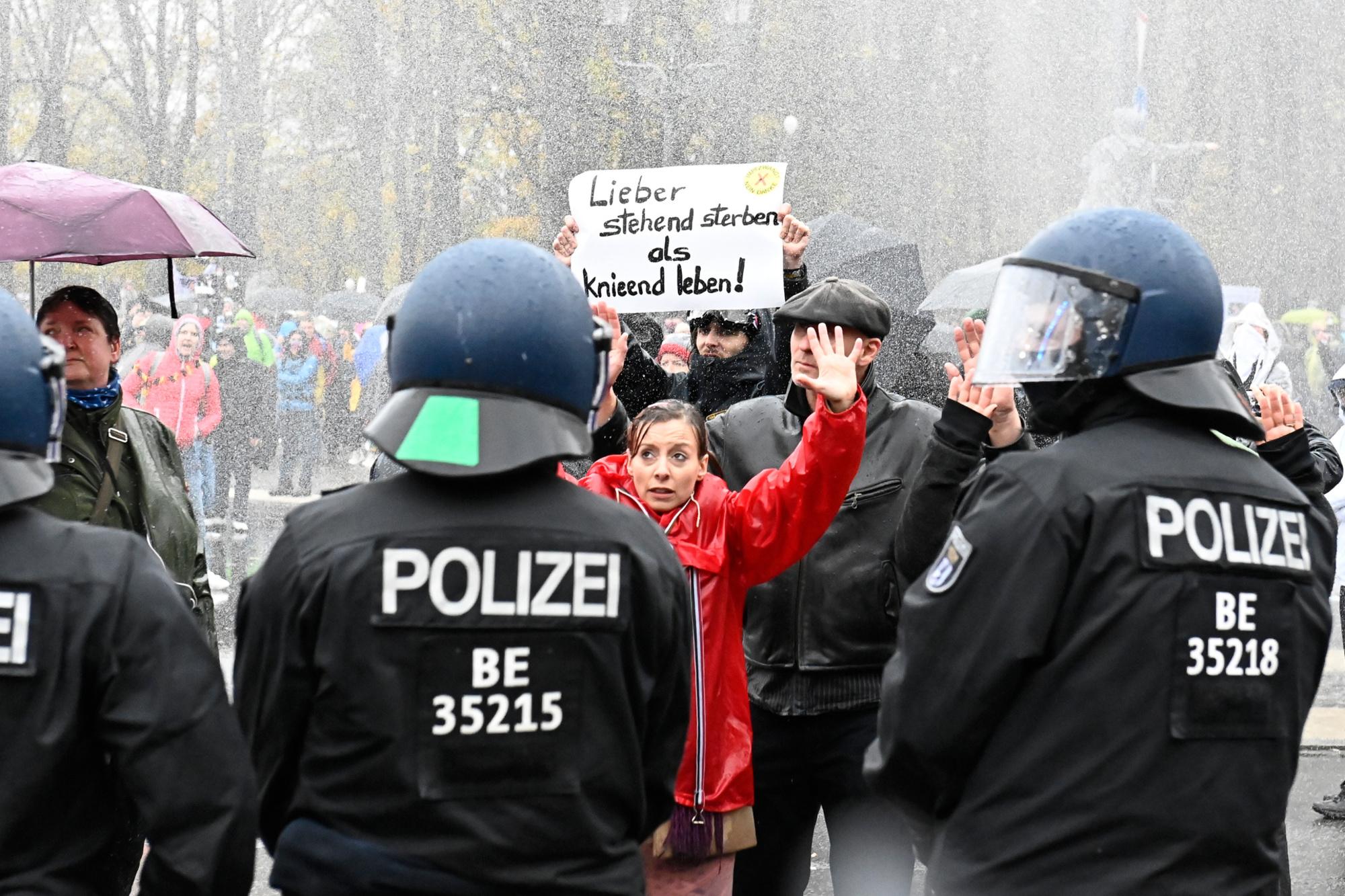 """Un manifestant brandit une affiche sur laquelle on peut lire """"Plutôt mourir debout que de vivre à genoux"""" alors que la police utilise un canon à eau pour disperser les manifestants qui protestent contre les mesures imposées par le gouvernement allemand pour limiter la propagation du coronavirus, le 18 novembre 2020 à la Porte de Brandebourg à Berlin., Belga Image"""