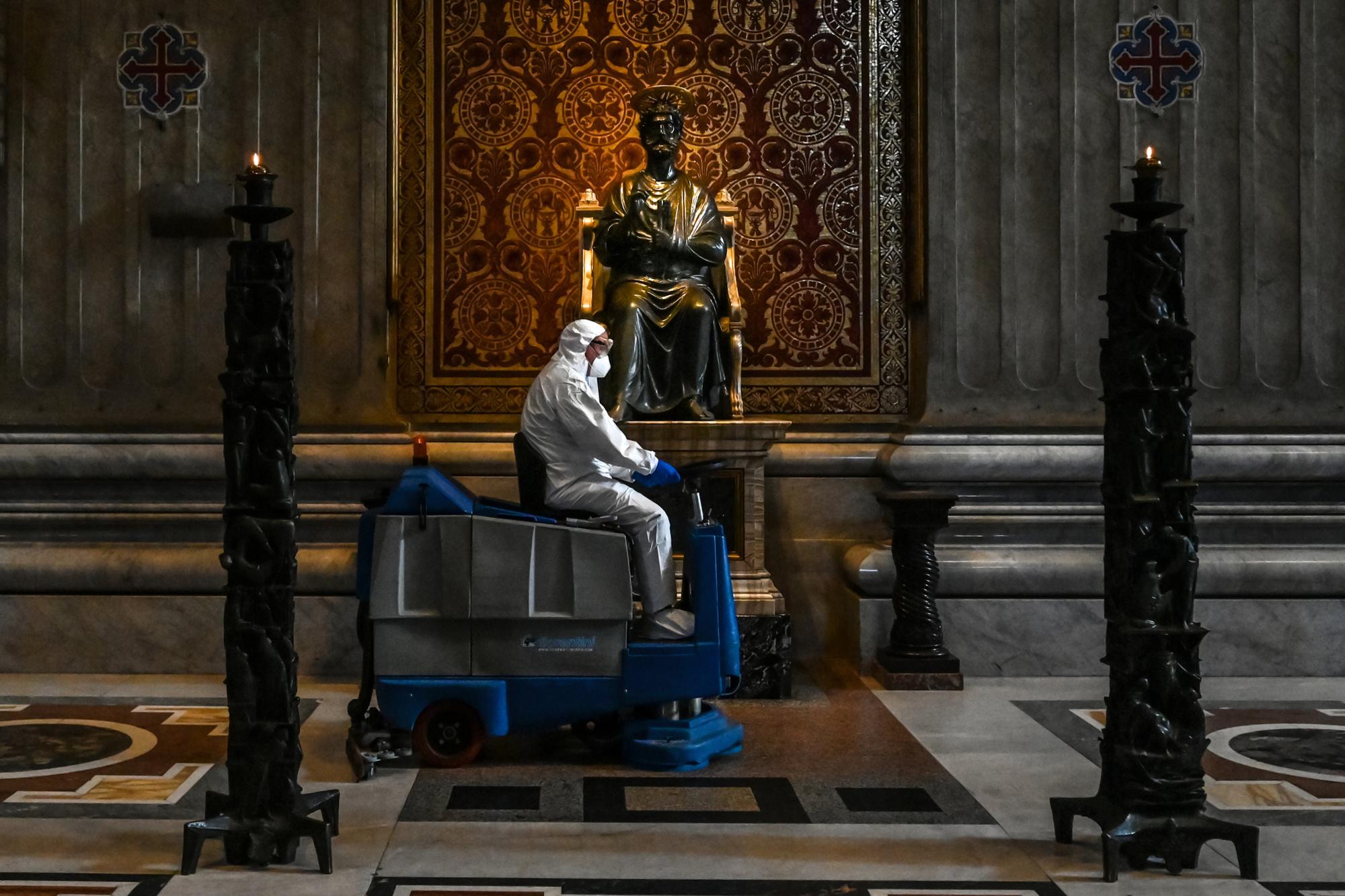 Un homme portant une combinaison de protection et un masque conduit une machine de nettoyage des sols devant une statue de Saint-Pierre lors de l'assainissement de la basilique Saint-Pierre au Vatican le 15 mai 2020, belga