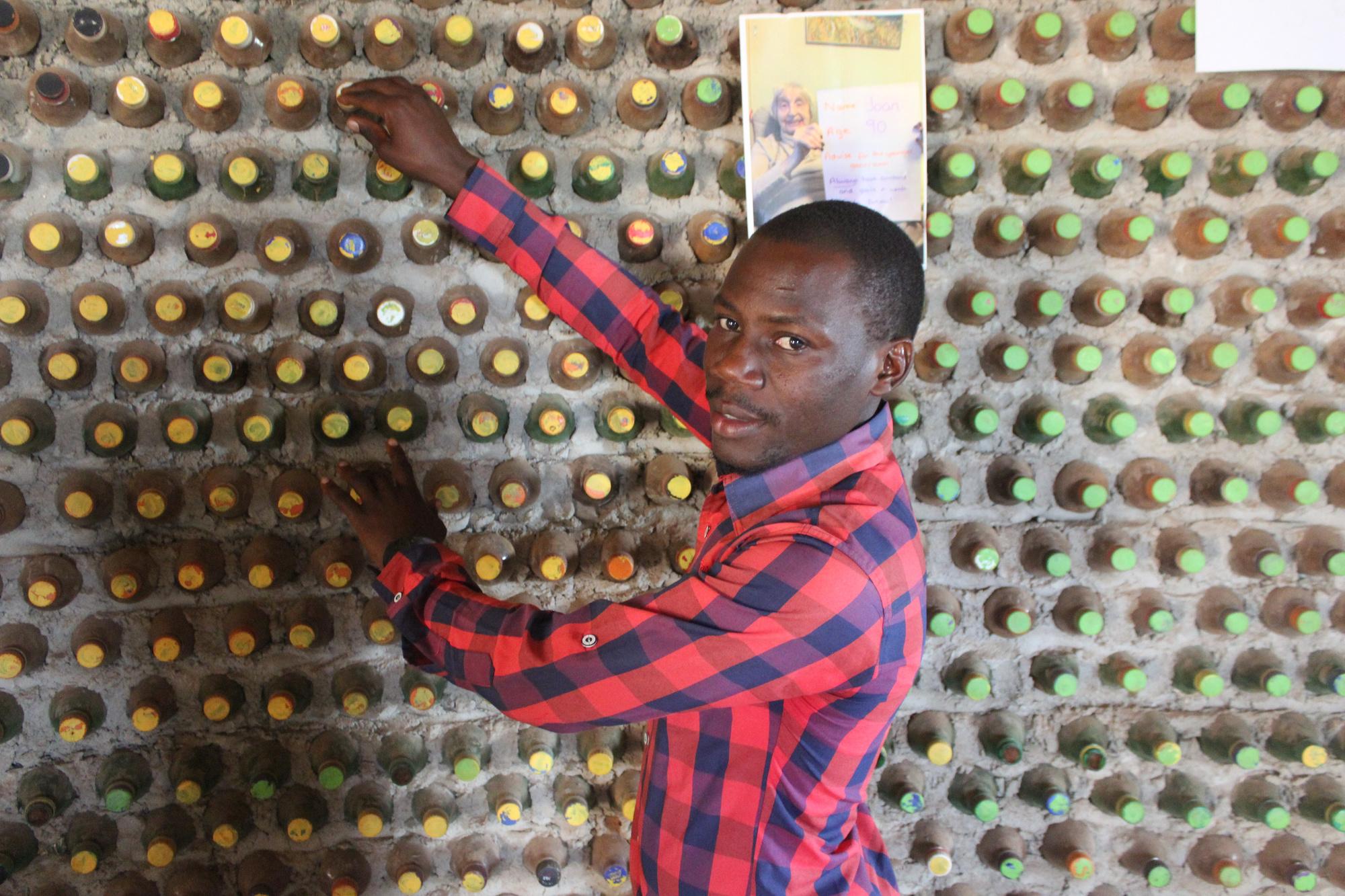David Mande in zijn huis opgetrokken uit ecobricks. De plastic flessen zijn gevuld met vochtige grond en harden uit tot een bouwsteen., Wambi Michael / IPS