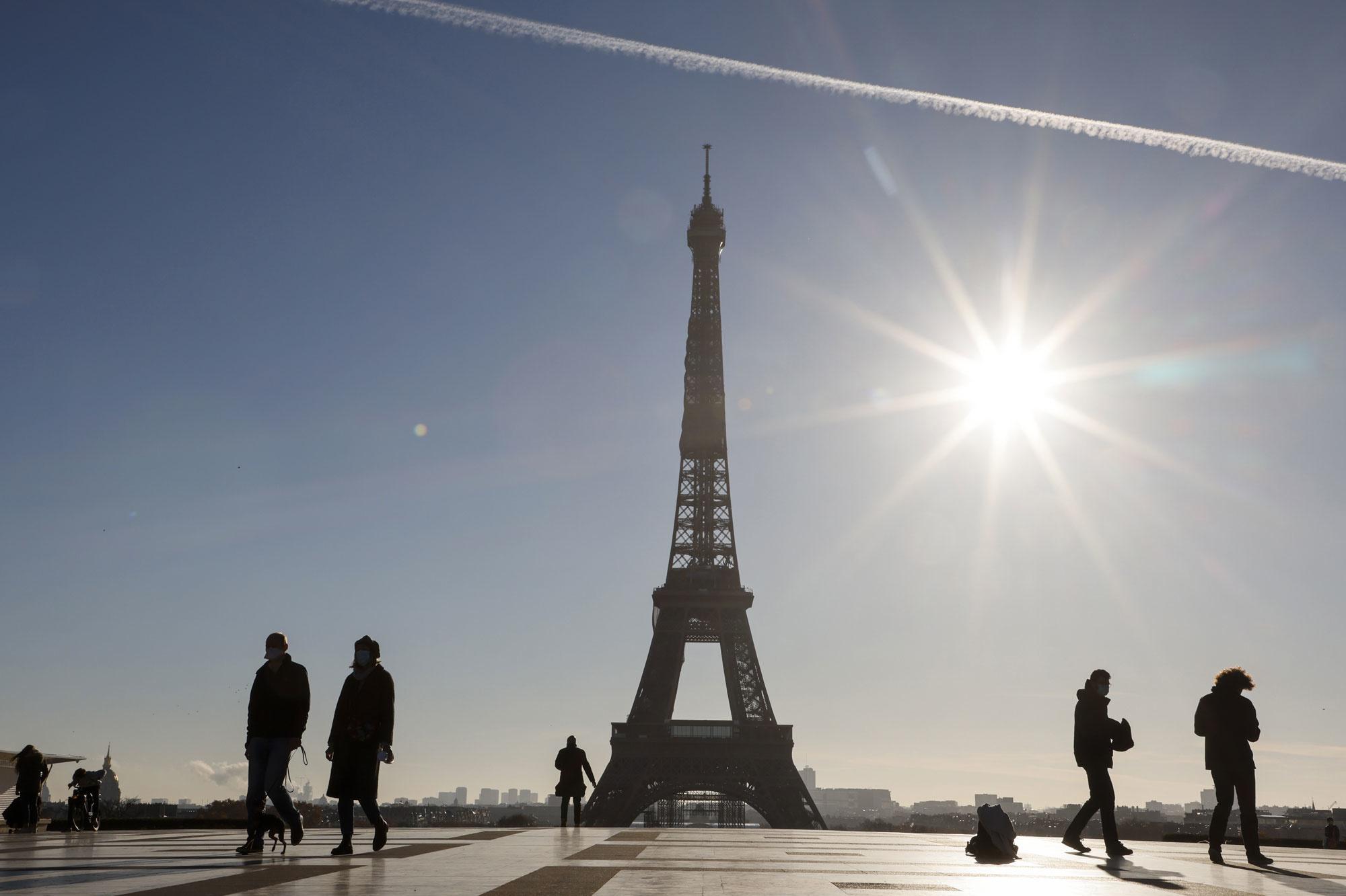 Des passants devant la Tour Eiffel, sur la place du Trocadéro à Paris, le 18 novembre 2020, lors d'un deuxième confinement visant à contenir la propagation de la pandémie de Covid-19., Belga Image