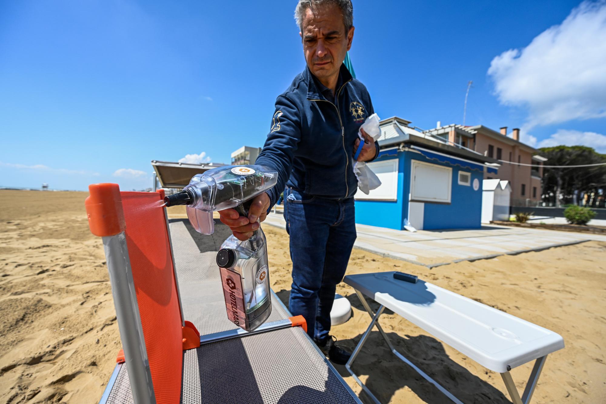 Un homme désinfectant un transat sur une plage privée à Jesolo, près de Venise., belga