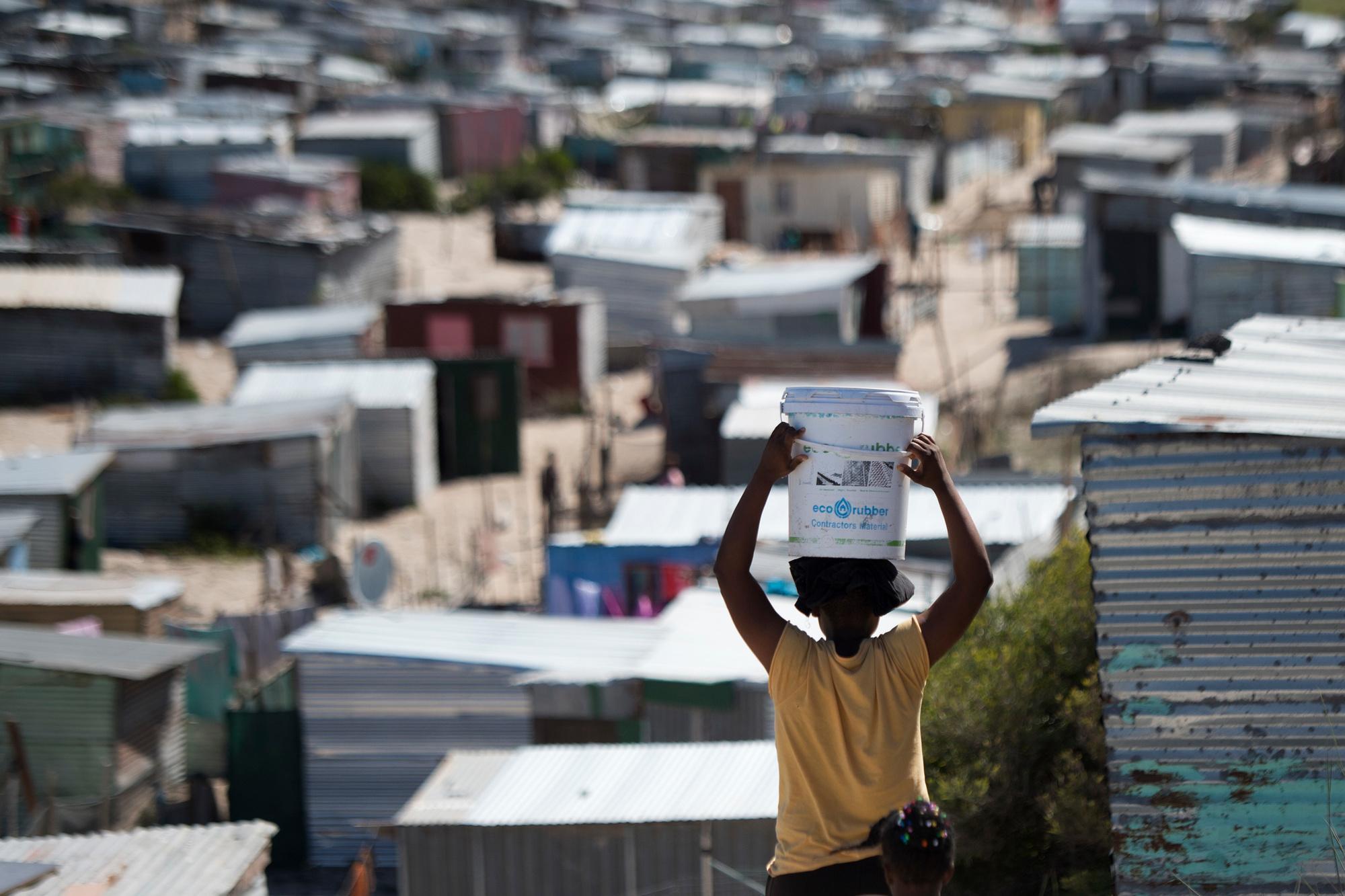 Une femme transporte un seau d'eau douce dans un établissement informel à Khayelitsha, près du Cap, au Cap. Les administrateurs des gouvernements locaux au Cap ont déclaré le 29 mars 2020 qu'un cas de coronavirus COVID-19 avait été détecté à Khayelitsha, le plus grand canton de la ville, où des centaines de milliers de personnes vivent dans des cabanes., belga