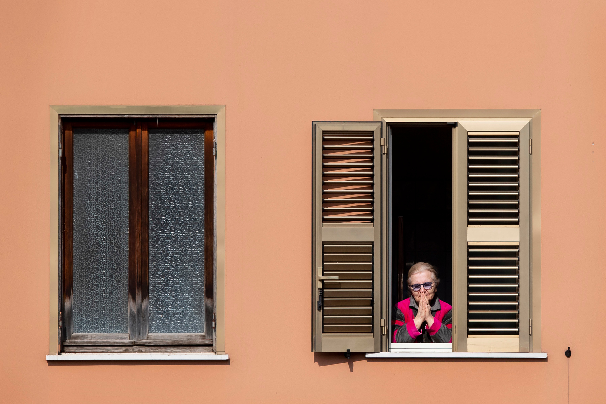 """""""Nu het duidelijk wordt dat ook gezonde jongeren risico lopen, en bovendien blijkt dat presymptomatische overdracht een duidelijke rol speelt bij de verspreiding, zou de vuistregel voor iedereen, jong en oud, moeten zijn: gedraag je alsof je COVID positief bent en beschouw iedereeen die je tegenkomt als potentieel positief."""" Foto: een oudere vrouw bidt tijdens de zondagsmis gehouden op het dak van de San Gabriele dell'Addolorata in Rome, 29 maart 2020., belga"""
