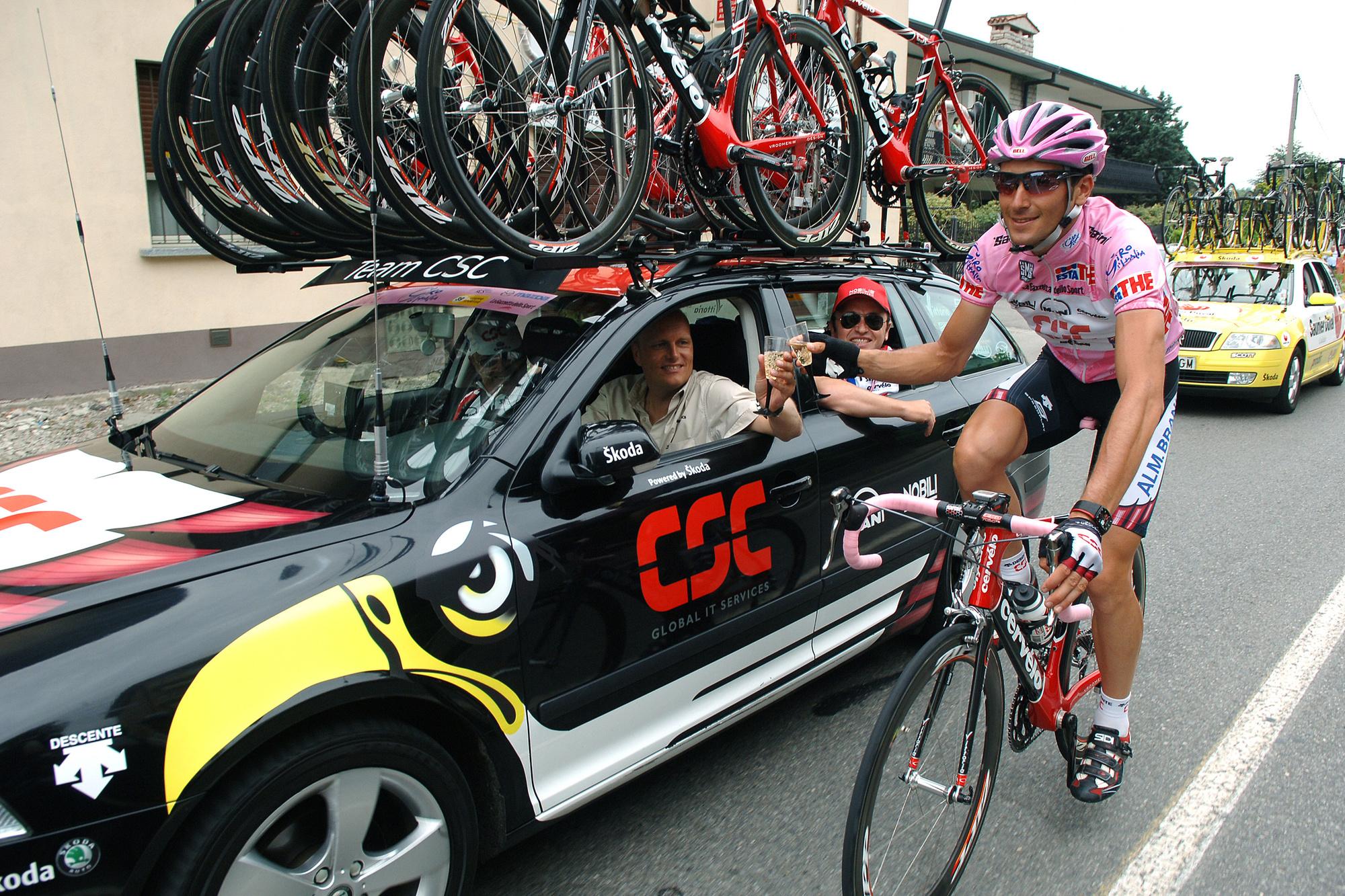 Basso bij zijn overwinning in de Giro in 2006 met ploegleider Bjarne Riis in de auti?, GETTY