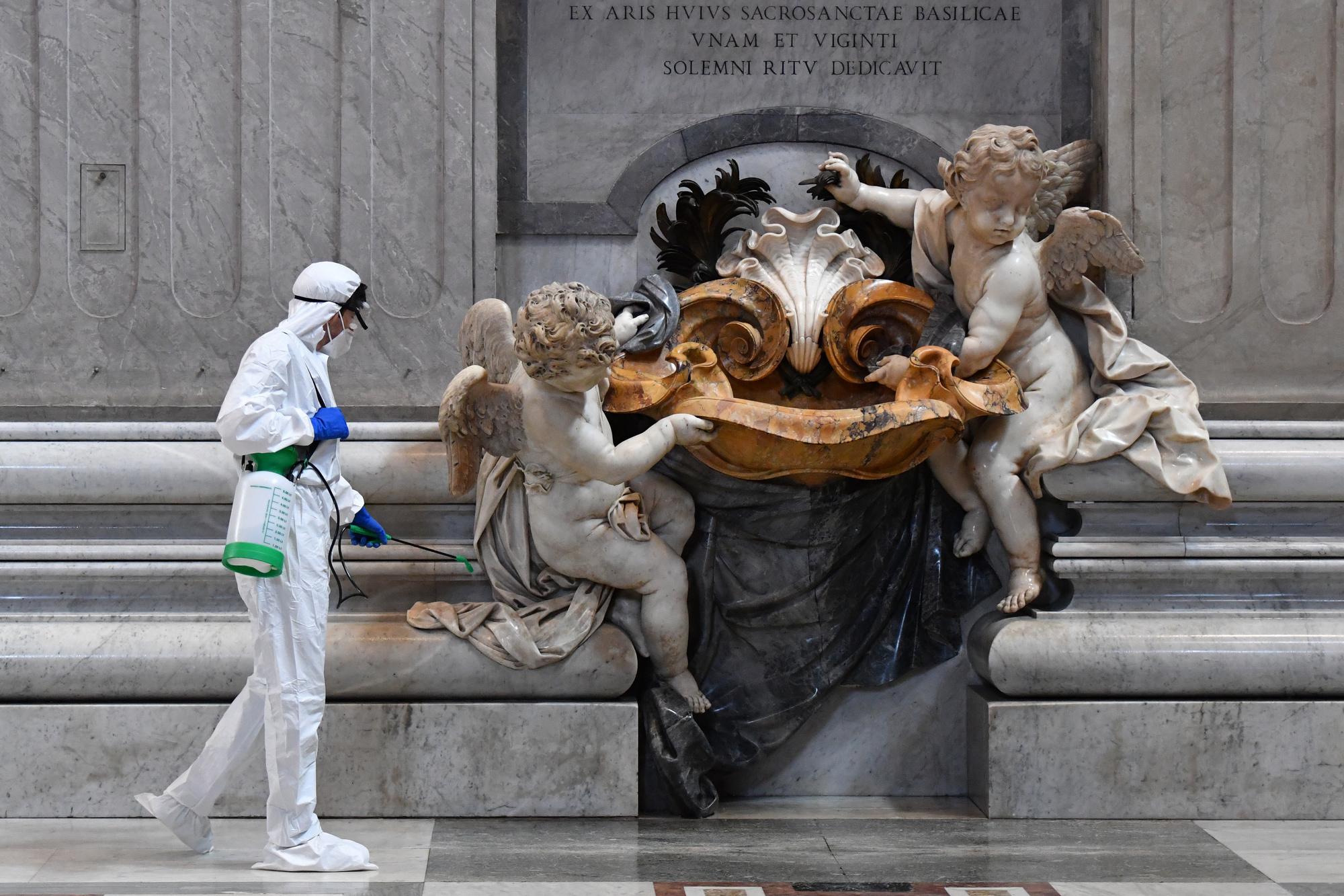 Un homme portant une combinaison de protection et un masque vaporise un désinfectant lors de l'assainissement de la basilique Saint-Pierre au Vatican le 15 mai 2020, belga