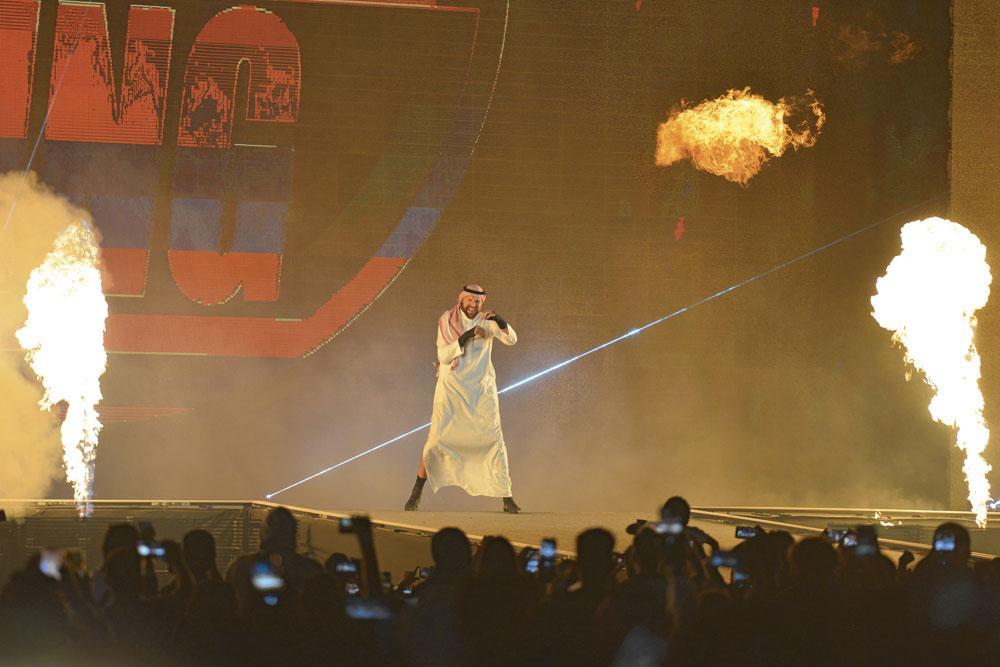 """Le Britannique Tyson Fury se dirige vers le ring en tenue saoudienne traditionnelle lors de son premier combat WWE. Cela lui a valu 14 millions d'euros et un combat """" gagné """"., belgaimage"""
