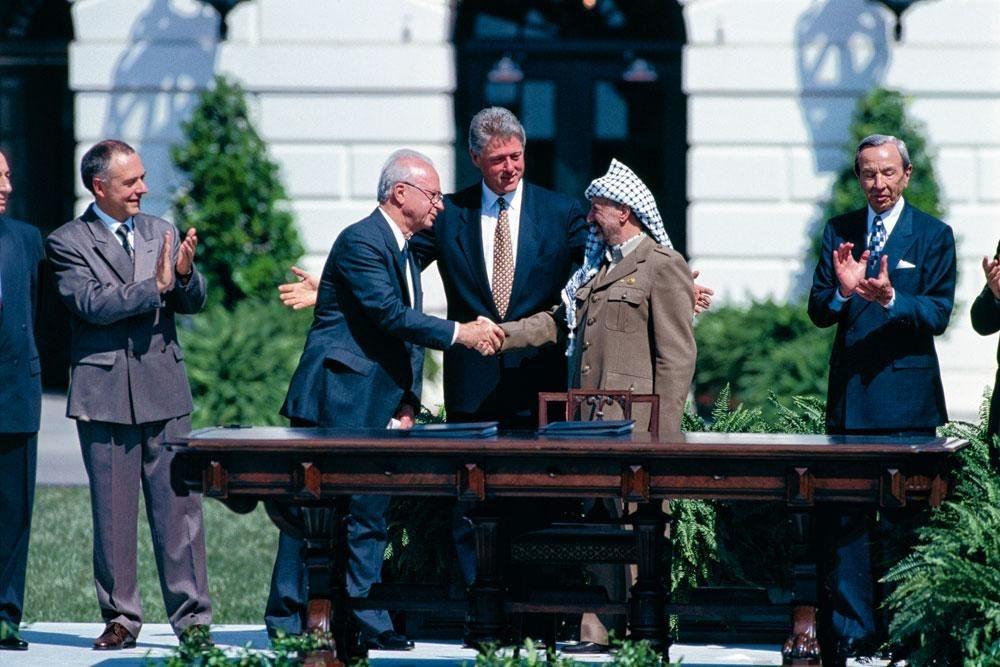 Sous le regard du président américain Bill Clinton, la poignée de main entre l'Israélien Yitzhak Rabin et le Palestinien Yasser Arafat, scellant les accords de Washington, le 13 septembre 1993., LARRY DOWNING/GETTY IMAGES