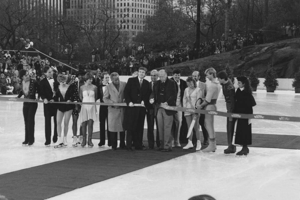 L'homme d'affaires américain Donald Trump (au centre, à gauche en long manteau foncé) lors de la cérémonie de réouverture de la patinoire Wollman à Central Park, New York, le 13 novembre 1986. Le maire de New York, Ed Koch (1924 - 2013), coupe le ruban., Getty Images
