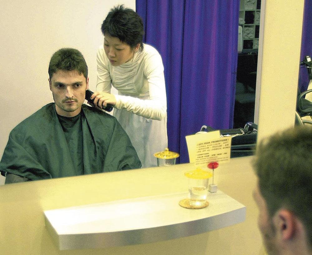In 2001 in Singapore: even naar de kapper gaan nadat hij de uit de gevangenis is vrijgelaten., belgaimage