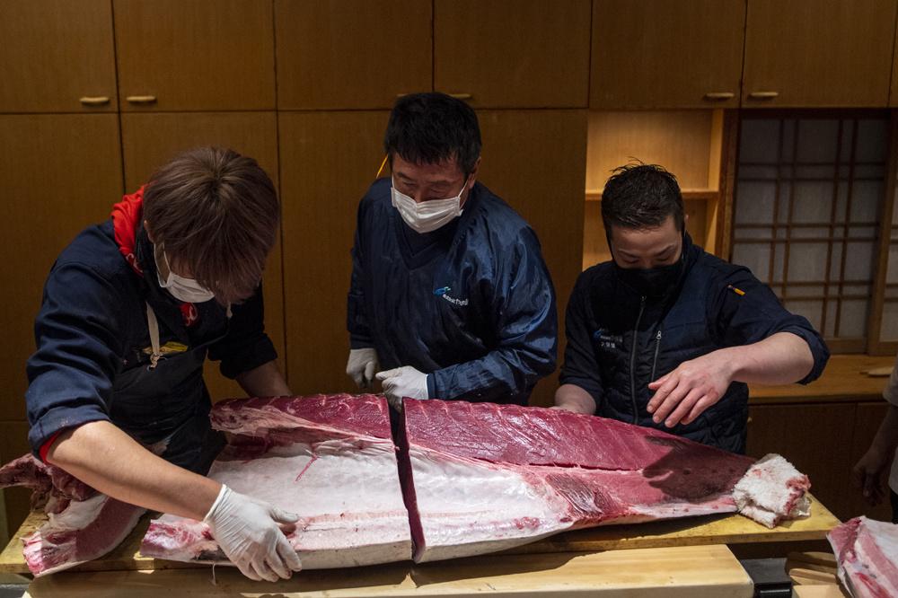 Yukitaka Yamaguchi et son équipe en pleine découpe de leur achat de janvier 2021, Belga Images