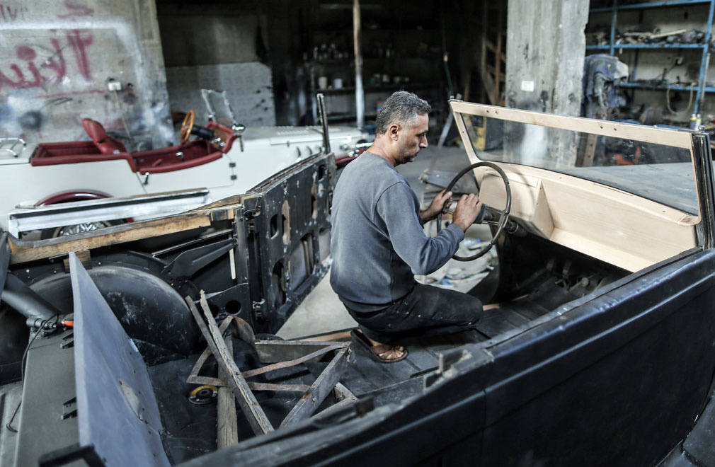 Dans son atelier de Gaza City, Mounir al-Chindy s'affaire minutieusement à l'intérieur d'une Armstrong Siddeley gris foncé., Belga