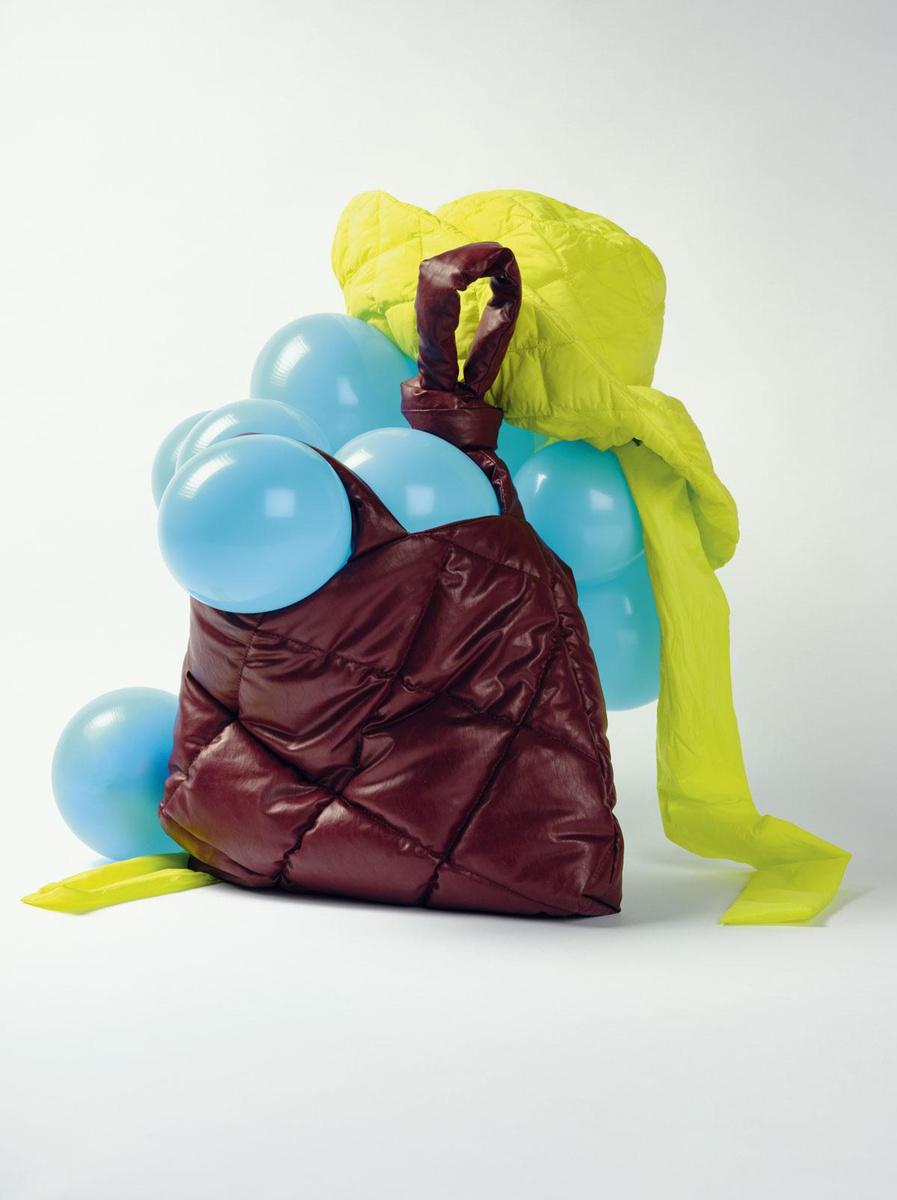 Sac à main matelassé en similicuir bordeaux, Kassl Editions @ de Bijenkorf. Chapeau en duvet jaune citron, Psophia. Ballons biodégradables en latex, Natural Fun @ festivalshop.be, BURP