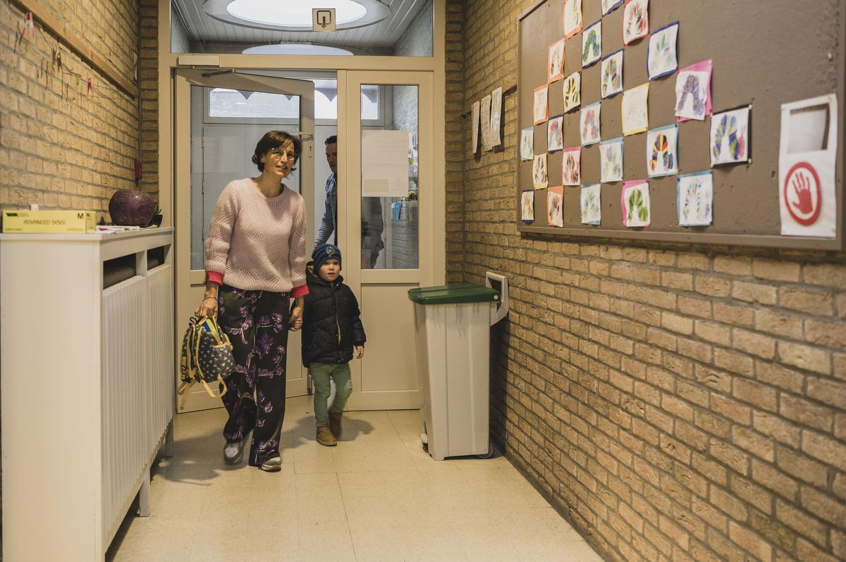Directeur Chantal Grymonprez begeleidt de kleutertjes bij het binnenkomen. Ouders mogen hun kinderen enkel afzetten aan de deur., Olaf Verhaeghe
