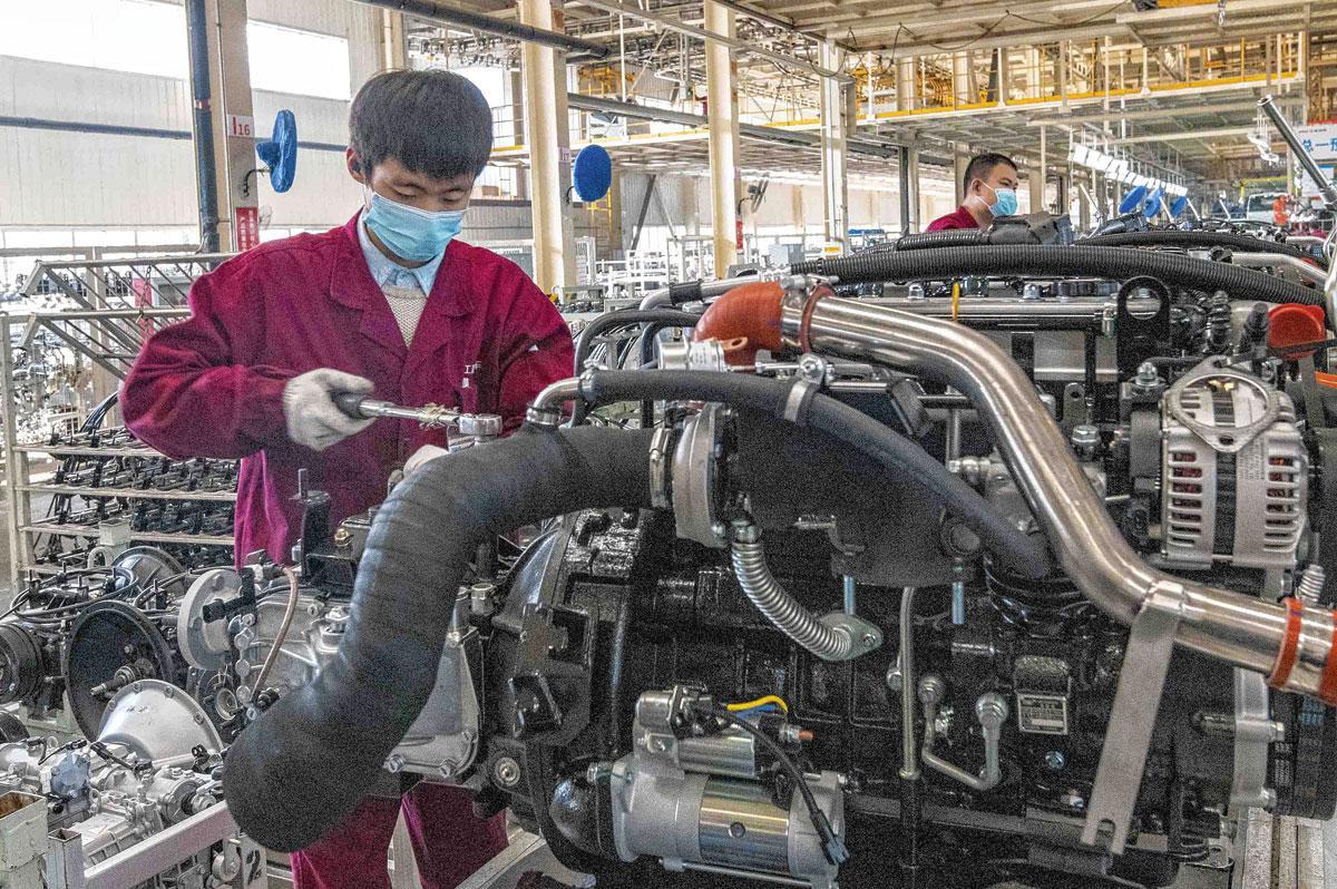 Chinese arbeider aan de assemblagelijn in een autofabriek in Qingzhou. 'Geen volk werkt harder en gedisciplineerder.', Getty Images