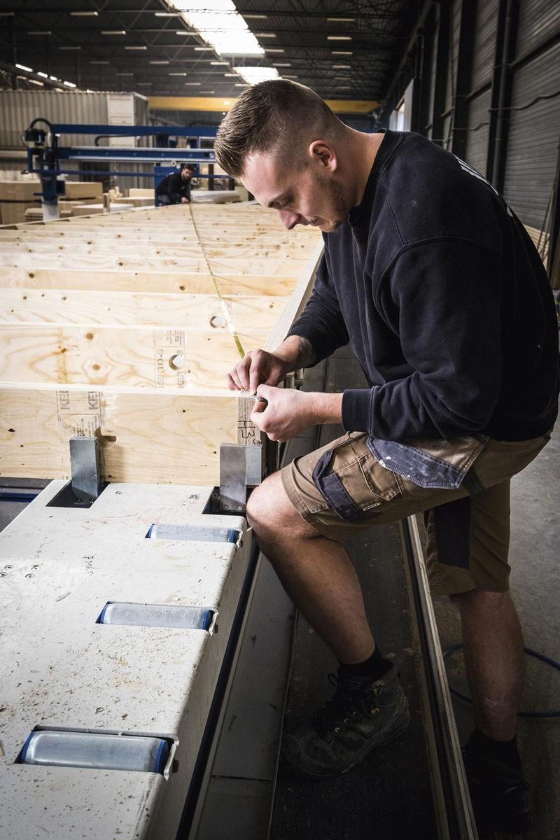 """3 Nagelen, lijmen en frezen In het verlengde van de zaagmachine staat de tweede machine, de MOBI-one: """"Die is speciaal voor ons ontwikkeld"""", zegt Timmermans. """"Het is een halfautomatische framingmachine waarmee we de kaders van de wanden, de vloeren en de daken maken."""" Een operator legt de balken op de machine. Via een katrolsysteem worden de platen aangebracht. """"De machine kan nagelen, lijmen en frezen. Al die toepassingen zitten op één station - vandaar de naam MOBI-one"""", vertelt Timmermans. Ook deze machine wordt automatisch aangestuurd met de BIM-software., FOTOGRAFIE WOUTER RAWOENS"""