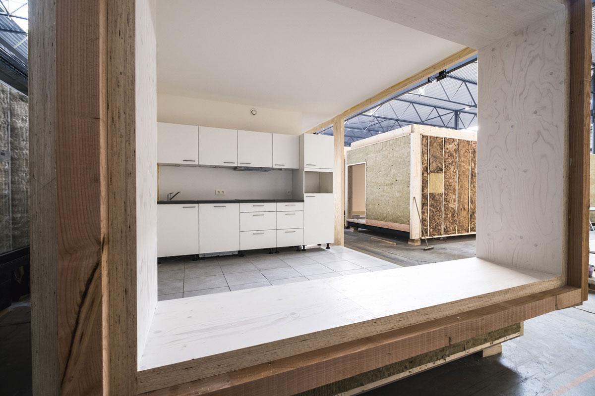 """5 Binnen- en buitenafwerking De vakmensen van Skilpod plaatsen de ramen en deuren, leggen de tegels en verzorgen het pleister- en schilderwerk. """"Zowel in de binnen- als de buitenafwerking houden we de keuze heel beperkt"""", zegt Timmermans. """"Zo kunnen de klanten alleen kiezen uit drie soorten tegels. Zonder die standaardisering levert modulair bouwen te weinig prijsvoordeel op tegenover klassiek bouwen."""" Voor de binnenwanden gebruikt Skilpod geen klassieke gipsplaten, maar fermacellplaten, die voor een belangrijk deel uit gerecycleerd materiaal bestaan. """"Die zijn veel steviger dan klassieke gipsplaten. Onze woningen worden afgewerkt naar de werf getransporteerd. Die platen moeten tegen een stootje kunnen."""" De gevels worden afgewerkt met steenstrips of hout., FOTOGRAFIE WOUTER RAWOENS"""