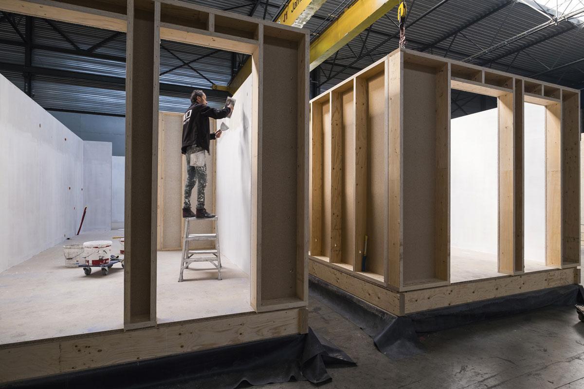 """4 Assembleren In de assemblageruimte worden alle componenten - vloeren, wanden en daken - manueel samengebracht. """"Boven op de vloerplaat monteren we altijd eerst de badkamer, waarna we de wanden en het dak toevoegen."""" In die fase wordt ook de elektrische bekabeling aangebracht., FOTOGRAFIE WOUTER RAWOENS"""