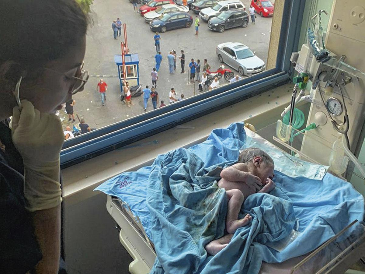 10 août 2020, Liban, Beyrouth : à l'hôpital Saint George, une infirmière s'occupe du nouveau-né George, fils d'Edmond Kneisher et de sa femme. George est né 15 minutes après l'explosion dévastatrice dans le port de Beyrouth. Lorsque la femme enceinte a été emmenée dans la salle d'accouchement, le courant a été coupé dans tout l'hôpital. Le médecin a poursuivi l'accouchement en utilisant les lampes de son smartphone., Edmond Khneiser/privat/dpa/Belgaimage)
