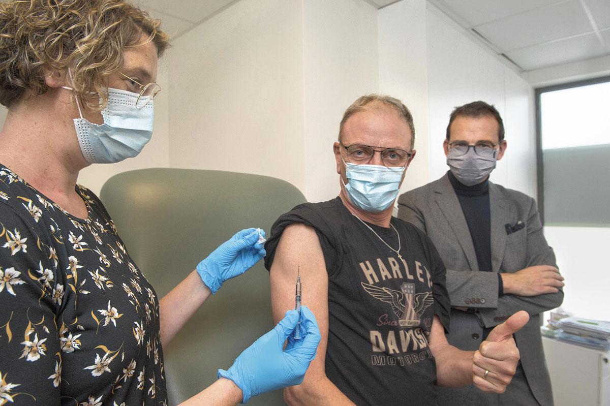 In goed gezelschap: huisarts Nele Beke vaccineert Michel De Munck. Wouter Beke staat er monkellachend bij., JDB