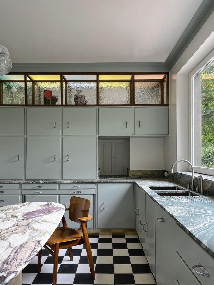La cuisine d'une habitation, à Tervuren, composée d'une table en marbre, de meuble Cubex récupérés et de niches en noyer, cernées de verres colorés et martelés (2021)., SDP / SÉBASTIEN CAPORUSSO