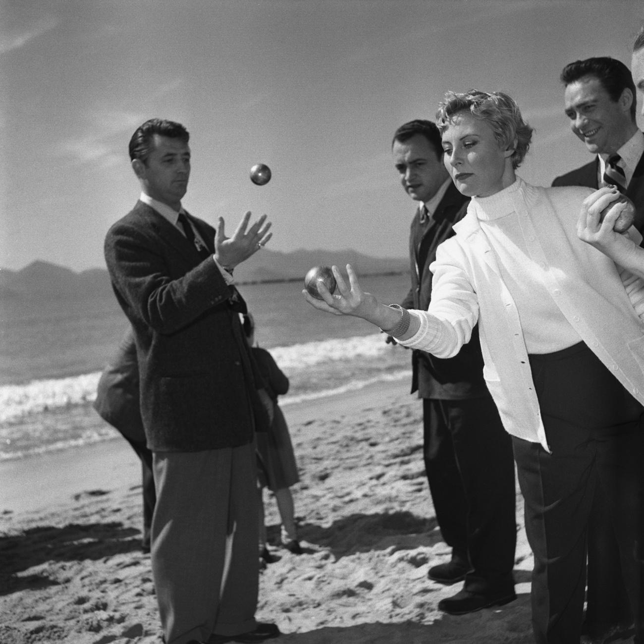 Festival de Cannes 1950 : Stars du moment, Robert Mitchum et Michèle Morgan dispute une partie de pétanque sur la plage, Getty Images
