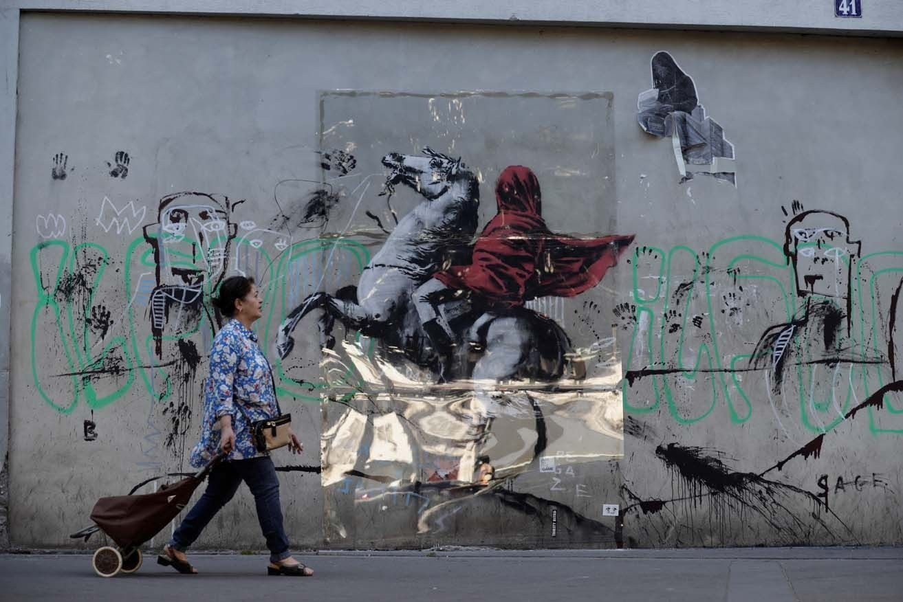 A woman walks past a recent artwork by anonymous street artist Banksy in Paris, on June 28, 2018. Following mutiple detorations of Banksy's work this week, art lovers allegedly protected with plexiglass his mural of Napoleon Bonaparte wearing a headscarf inspired by the original painting by Jacques-Louis David, in the 19th arrondissement of Paris. / AFP PHOTO / Thomas SAMSON, AFP