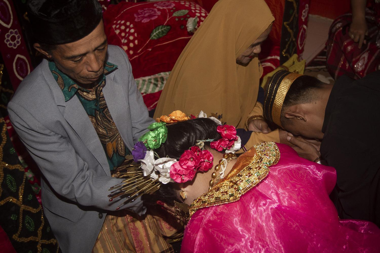25 juillet 2020 : Lia, 18 ans, et son mari Randi, 21 ans, demandant la bénédiction de leurs parents après s'être mariés dans le village de Tampapadang à Mamuju, dans le Sulawesi occidental. Le mariage d'enfants est depuis longtemps courant dans les communautés traditionnelles, de l'archipel indonésien à l'Inde, au Pakistan et au Vietnam, mais leur nombre a diminué à mesure que les organisations caritatives progressaient en encourageant l'accès à l'éducation et aux services de santé pour les femmes., AFP