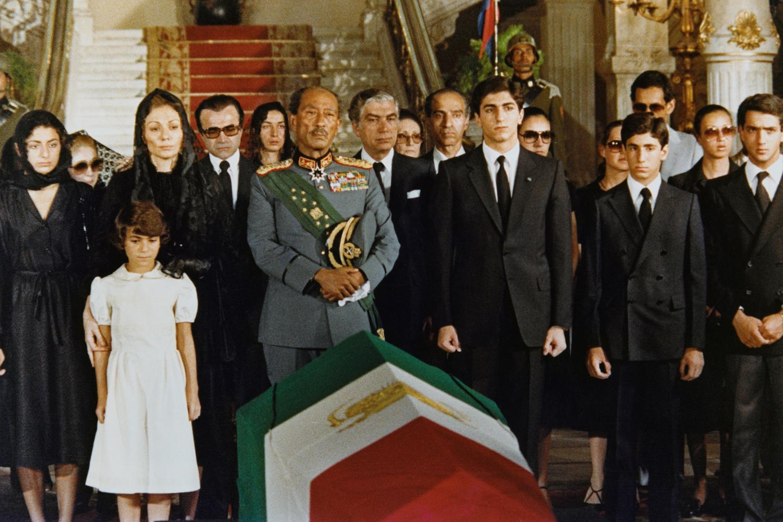 Le cercueil drapé du drapeau iranien, portant le corps de l'ex-Shah d'Iran tel qu'il repose dans le palais Abdin. De gauche à droite, la soeur jumelle du Shah, Ashref, la princesse Farahnas Pahlavi, 16 ans ; la princesse Laila Pahlavi, 9 ans ; la veuve du Shah, l'ancienne impératrice Farah Diba ; le président égyptien Anouar El-Sadate ; le prince Resa, 19 ans ; le prince Aly Pahlavi, 13 ans ; et le fils du président El-Sadate, Gamal., Getty Images