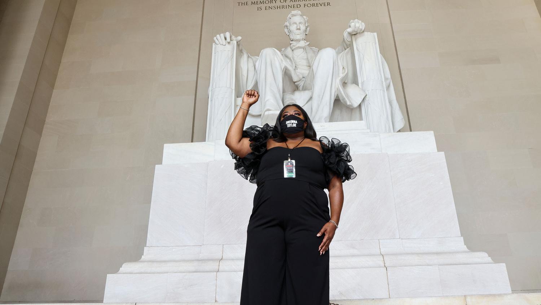 """DeJuana Thompson, de l'organisation Woke Vote, porte un visage de Breonna Taylor alors qu'elle attend à l'intérieur du Lincoln Memorial pendant la """"Commitment March : Get Your Knee Off Our Necks"""", une manifestation contre le racisme et la brutalité policière, le 28 août 2020, à Washington DC., Getty Images"""