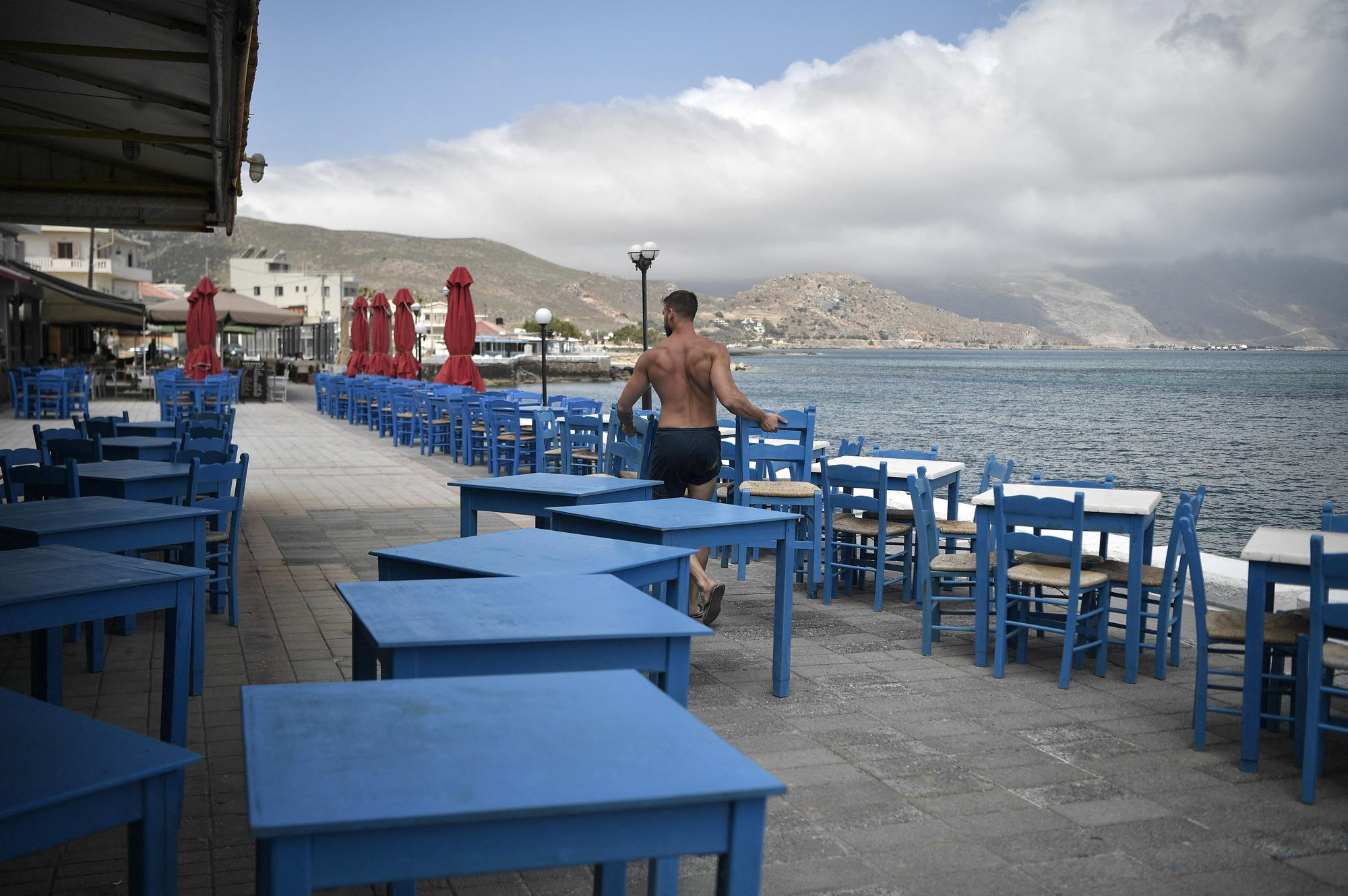 Alexandros Koukourakis, prépare la terrasse de sa taverne, à Kissamos, AFP