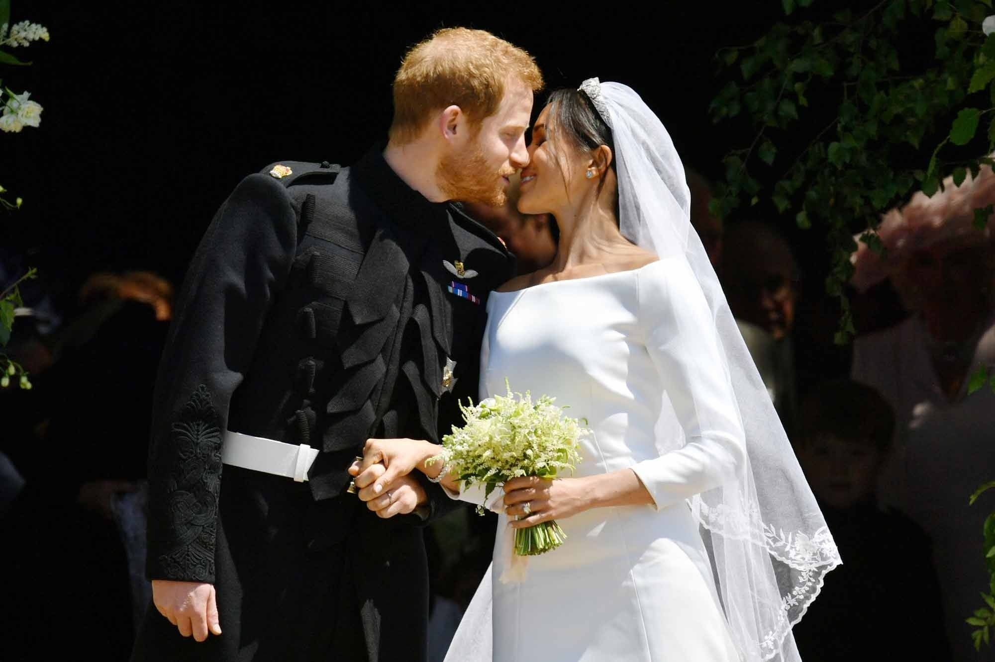 Britain's Prince Harry, Duke of Sussex kisses his wife Meghan, Duchess of Sussex as they leave from the West Door of St George's Chapel, Windsor Castle, in Windsor, on May 19, 2018 after their wedding ceremony. / AFP PHOTO / POOL / Ben Birchall, AFP