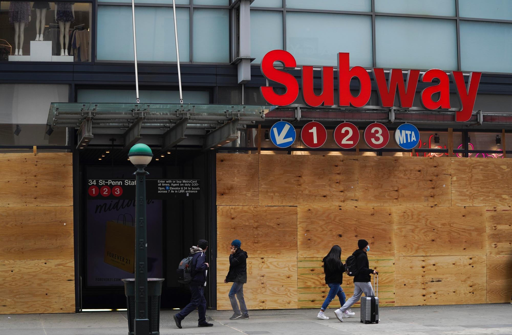 Wandelaars stappen voorbij dichtgetimmerde winkels in New York, 2 november 2020. , Belga
