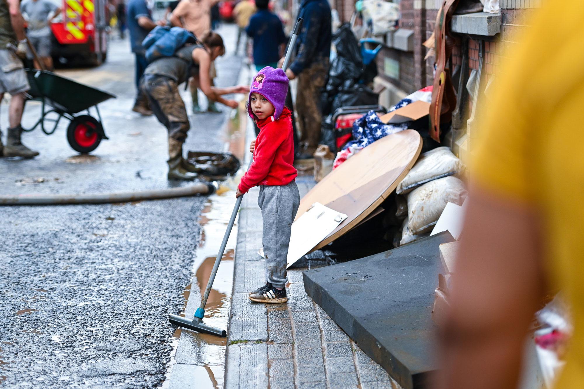 Een kind helpt bij het opruimen na de overstromingen in de stad Namen, 25 juli 2021., Belga